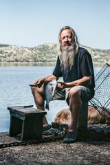 portrait of an old fishermen with long hair and white beard cleaning a freshly caught fish