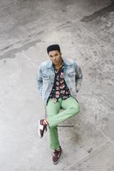 Stylish young black man sitting wearing green pants