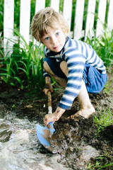 boy playing in the mud with shovel