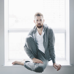 Man in a grey hoodie and sweat pants sits at a window