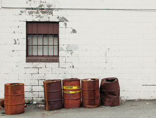 Rusty oil drums by a brick wall