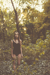 Young woman standing in the forest.