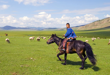 Boy riding a horse in a beautiful scenic view of nature.