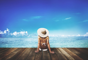 Woman tanning on a deck next to the beach