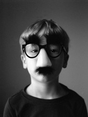 portrait of a little boy being serious with silly mustache glasses on