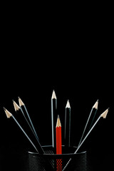 one smaller red pencile among a group of other black pencils before black background