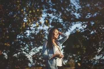 happy, thoughtful teen girl enjoying nature at sunset