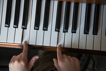 Child experiments with playing notes on a piano