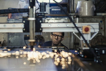 Young working man supervising plasma cutting machinery