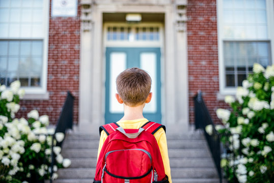 Boy wearing red backpack stands looking at the front entrance of a school