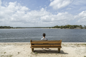 Teenage boy sitting on a wood bench looking out the water