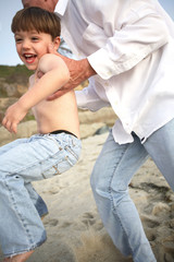 Man in white shirt holding laughing boy while running on beach