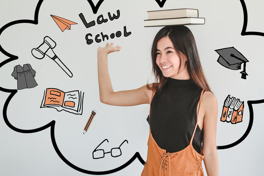 Young asian Student woman holding book with law achool doodles .