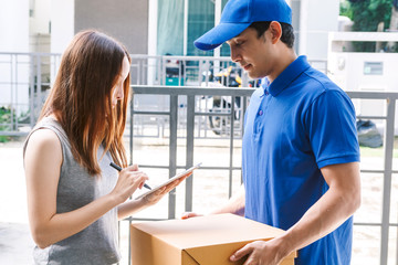 Woman putting signature in tablet and cardboard box with delivery man