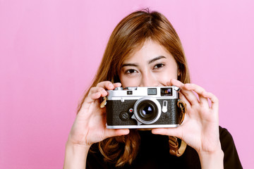 Fashion photo of young girl posing with vintage camera in hand on pink background