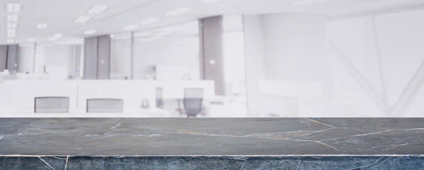 Black marble stone tabletop and blurred bokeh office interior space background - can used for display or montage your products.