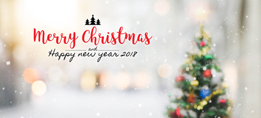 Christmas and Happy new year 2018 on blurred bokeh christmas tree with snowfall background.
