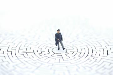 Miniature people: Businessman standing on center of maze