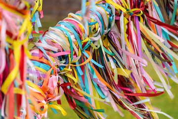 Multicolored ribbons tied up on the tree of desires close-up.