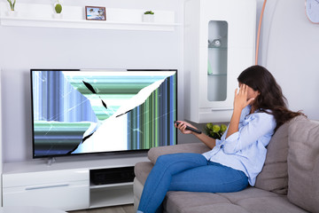 Woman Sitting On Sofa With Broken Television