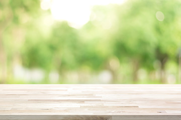 Wood table top on blur green background of trees in the park