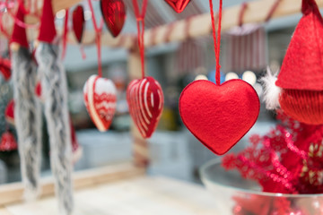 Hanging fabric heart ornaments on rope for Christmas decoration against blurred background.