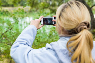 A blonde woman using a phone takes a photo of a beautiful landscape