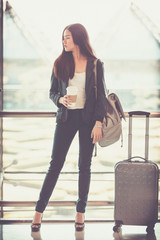 Airport woman holding disposable cup of coffee in hand