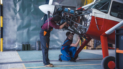 Two mechanics working on a small aircraft in a hangar with the cowling off the engine as they perform a service or repair Wall mural