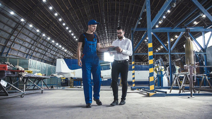 Mechanic and flight engineer having a discussion together as they stand in aircraft in a hangar.