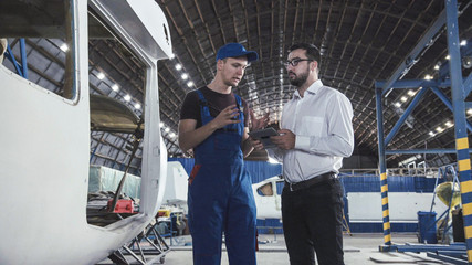 Aircraft mechanic and draftsman standing near plane carcass and talking with each other.