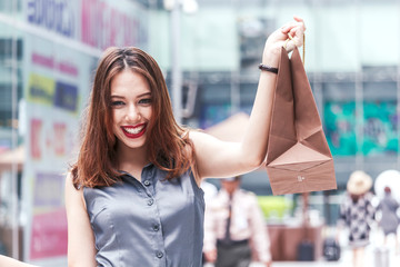 Woman holding shopping bag walking on the street