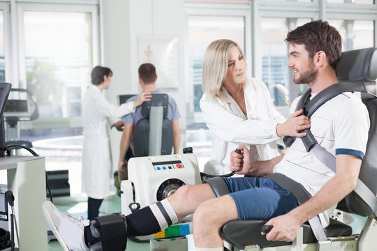 gym physiatric rehabilitation/ physicians with patients in a gym for physical rehabilitation dynamometer in the foreground and in the background cycle ergometer