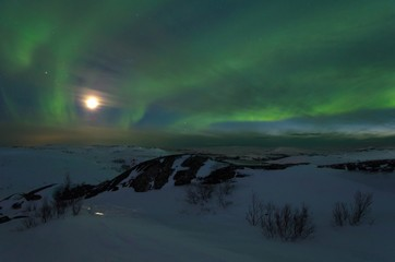 Northern lights,Aurora and moon in the night above the hills.