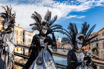 Carnival masks on bridge against Grand Canal in Venice, Italy