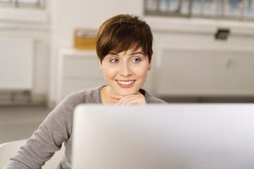 frau schaut lächelnd auf ihren computer