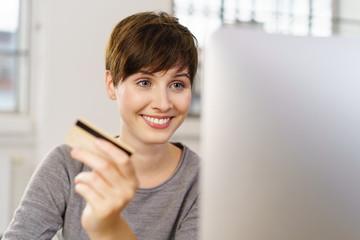 lächelnde frau bestellt im internet und zahlt mit kreditkarte