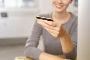 frau sitzt am pc und schaut lächelnd auf ihre kreditkarte