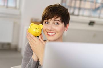 lächelnde frau sitzt am computer zeigt ihr sparschwein