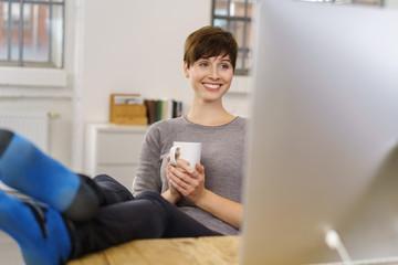 entspannte frau schaut auf ihren computer und legt die füße auf den tisch