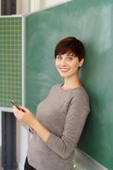 frau lehnt in der schule an der tafel und hält ihr mobiltelefon in der hand