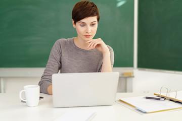 lehrerin schaut auf ihren laptop