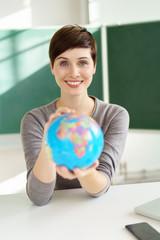 lächelnde lehrerin zeigt einen globus