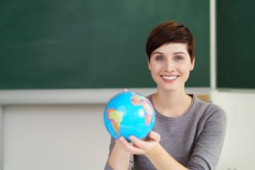 lächelnde lehrerin zeigt einen globus im unterricht