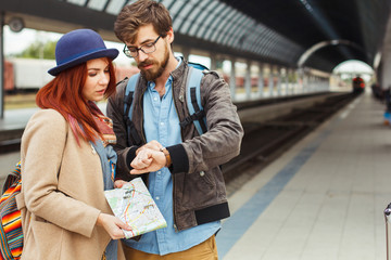 Hipster Traveller couple looking at smart watch while waiting for the train at railway station. Autumn time. Woman holding a map. Man with backpack. Copy space. Travel concept