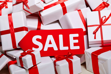 The red discount is on the mountain of white gifts with a red ribbon.Sales, purchases, black Friday, packaging, shop, bargain, sales, advertising, inexpensive.new year, christmas, profitable.