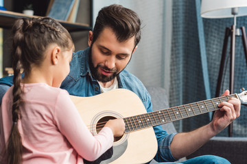 father learning daughter to play guitar
