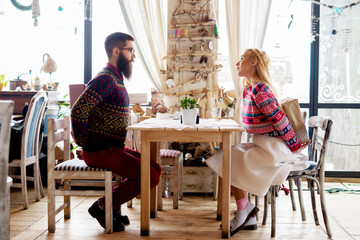 Young lovely hipster love couple in a sweater sitting in a restaurant and holding gifts behind their backs for a surprise.