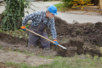 Construction worker digging trench using shovel, hole for wall foundation or pipeline