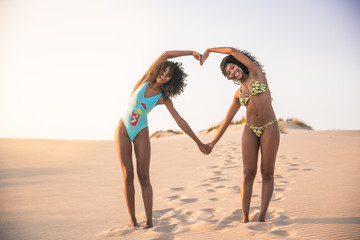 Laughing girlfriends showing heart with hands on the beach